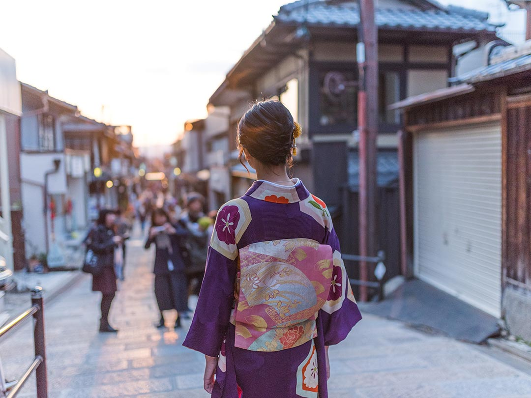 Editorial photo: Back of woman standing in street wearing traditional Japanese garment