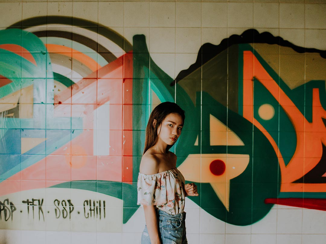 Editorial photo: Asian woman in front of graffiti wall