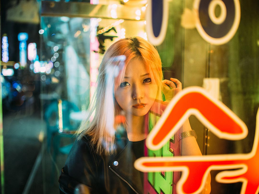 Editorial photo: Asian female staring from inside a shop window