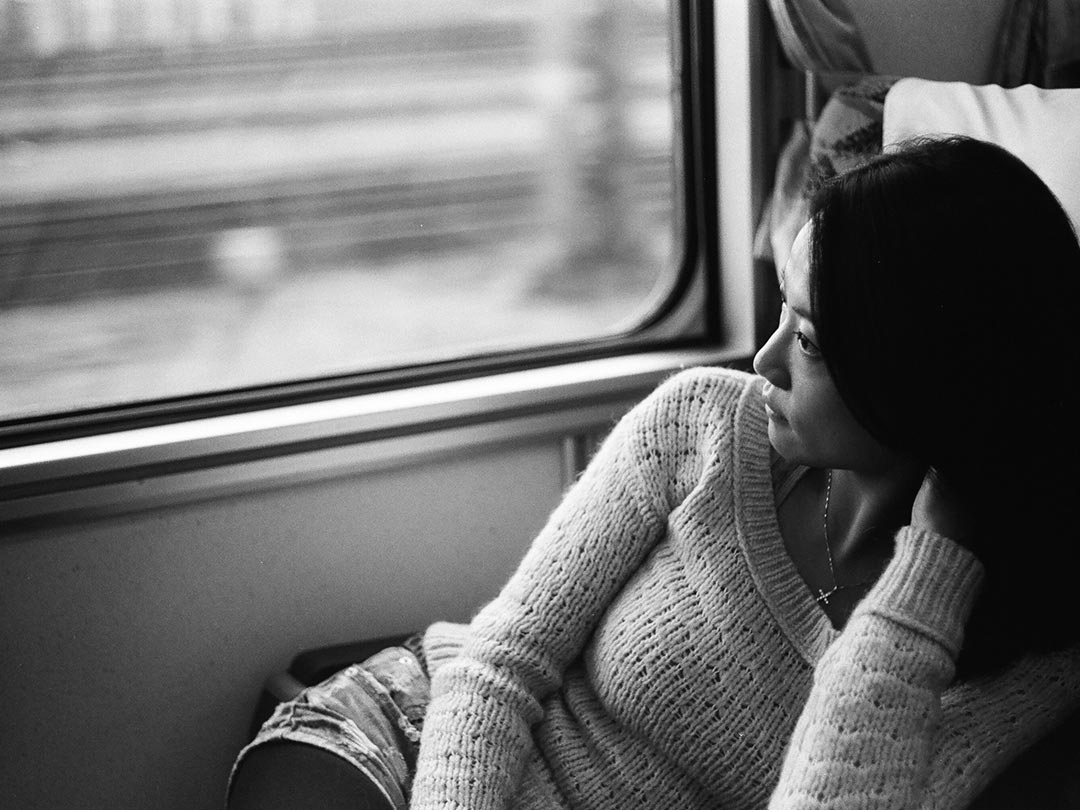 Editorial photo: Asian woman gazing out window on a buss or train