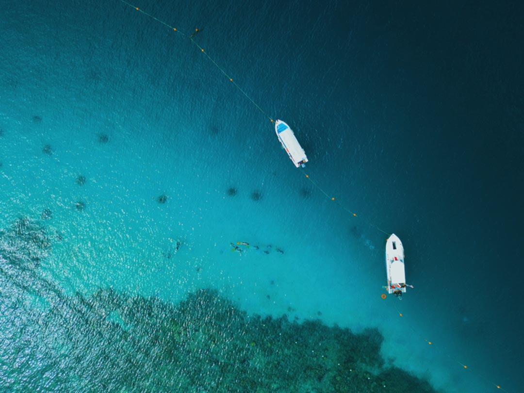 Photo: Bird's eye view of open sea with 2 boats