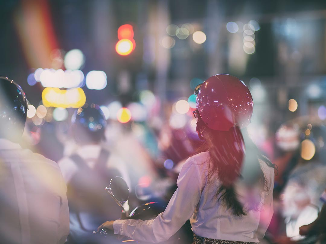 Editorial photo: Vietnamese female on an electric scooter in night traffic